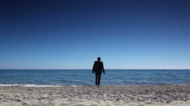 Man in suit stand on beach, then walked and immersed sea water and swam — Stock Video