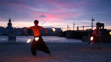 Two men make fire dancing on coast of Neva — Stock Video