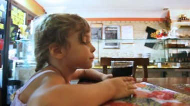 Little girl sits at table and drink from glasses carbonated water — Stock Video