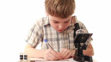 Chłopiec siedzi w pobliżu mikroskopu pisze coś w notatniku — Wideo stockowe