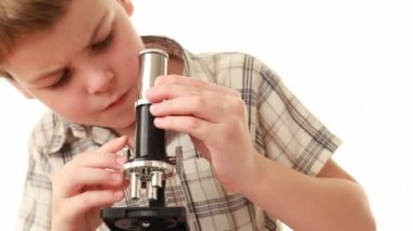 Little boy works with microscope making some research — Stock Video