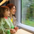 Stock Video: Mother with daughter ride in speeding train and look at window