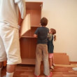 Stock Video: Father and kids construct wooden closet at home