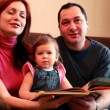 Parents and baby girl are sitting on the sofa considering book — Stock Video
