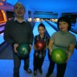Family of three stay with balls in hands in bowling club — Vídeo de stock