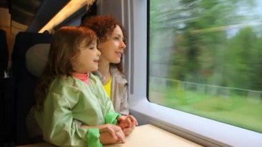 Mother with daughter ride in speeding train and look at window — Stock Video