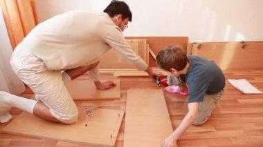 Padre apretarlos en tablero y chico trabaja con martillo en piso — Vídeo de Stock