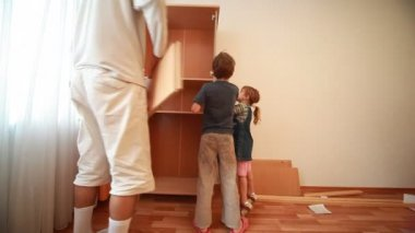Father and kids construct wooden closet at home — Stock Video