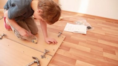Little boy construct piece of wooden furniture on floor — Stock Video