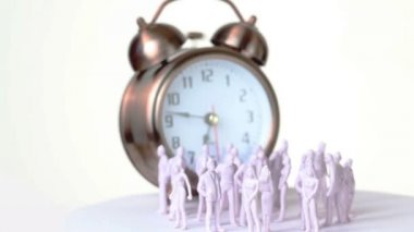 Little uncolored toy men and women stand in front of big clock which ringing — Stock Video