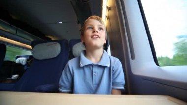 Leende pojke sitter och ser av fönstret tåg under rörelse — Stockvideo