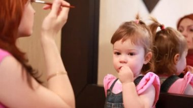 Woman doing makeup in front of the mirror, and her daughter sitting near — Stock Video