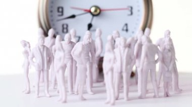 Little colorless toy men and women stand in front of big clock — Stock Video