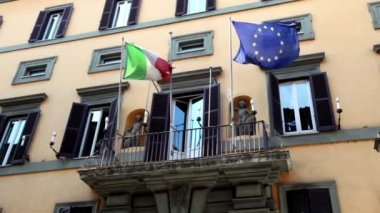 Wall of the building with balcony it is fitted flags of Italy and the EU — Stock Video