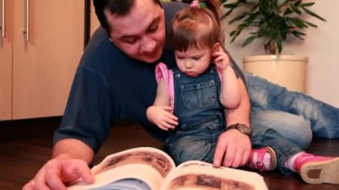 Father and baby girl are lying on the floor considering book — Stok video