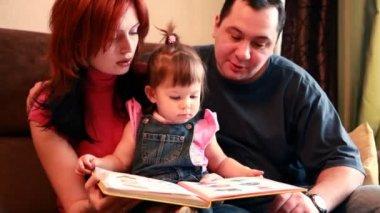 Ouders en babymeisje zitten op de bank overweegt boek — Stockvideo