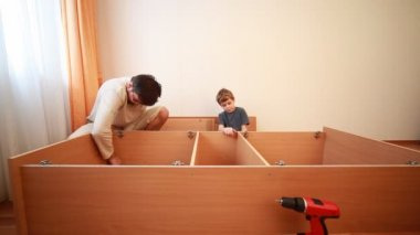 Father and son construct wooden cabinet at home — Stock Video