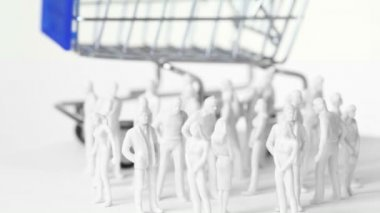 Little colorless toy men and women stand in front of big shopping trolley — Stock Video