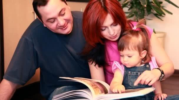 Parents et bébé fille sont assis sur le sol, considérant le livre — Vidéo