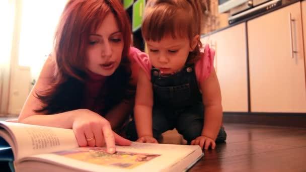 Maman et bébé fille sont étendus sur le sol, considérant le livre — Vidéo