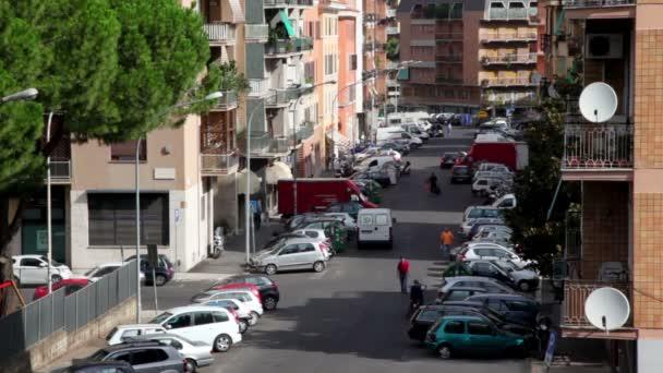 Pueblo calle arriba, muchos coches aparcados a ambos lados, los peatones caminar — Vídeo de stock