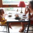 Mother and daughter eat breakfast sitting at table — Stock Video