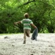 Boy runs, then he stops and runs back across meadow all strewn fluff — Stock Video