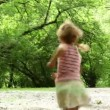 Girl runs away across forest meadow all strewn fluff — Stock Video