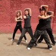 Stock Video: Dance team of four girls start dance synchronously