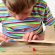 Stock Video: Boy apply adhesive and attach tail to wooden aircraft