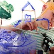 Stock Video: Boy draws picture of colored paint on transparent glass