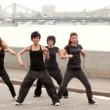 Stock Video: Four girls stand one by one and start dance in modern style synchronously on quay
