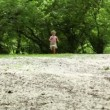 Girl runs closer from far across meadow all strewn fluff — Stock Video
