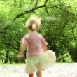 Girl hopping and runs away across meadow all strewn fluff, then she stops and touch her nose — Stock Video