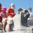 Mother and her kids sit on statue of lion near Flaminio obelisk — Stock Video #28844371