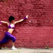 Flexible girl dances near red brick wall — Stock Video #28844383