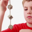 Stock Video: Boy hold chain compound of magnet spheres cubic structures