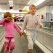 Stock Video: Boy and girl walk together by travelator in airport