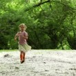 Stock Video: Girl runs closer across forest meadow all strewn fluff