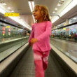 Stock Video: Little girl goes on automatic track in airport