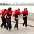 Stock Video: Four girls dance synchronously on quay, then turn around and dance