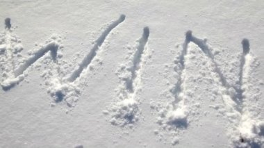 Word WINTER writen by stick on snow, shown in motion