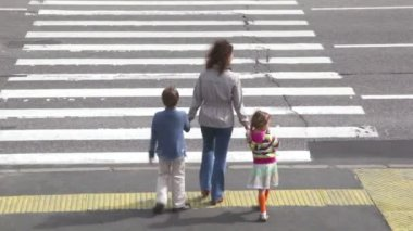 Mother and children, cross road at pedestrian crossing after car drove — Stock Video