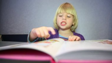 Little blonde girl considers pictures in the book — Stock Video