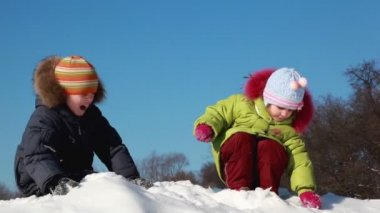 Kids enjoy play snowballs, girl chuck snow to boys face and he become displeased — Stock Video