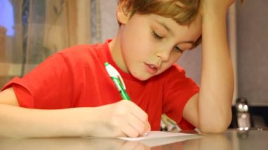 Close-up of boy very attentively writes something — Stock Video