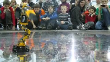 Children watch at two robots dancing during ROBOFEST-2011 — Stock Video