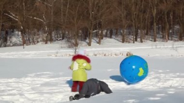 Kids boy and girl play with inflated ball, they push it and jump on — Vídeo Stock