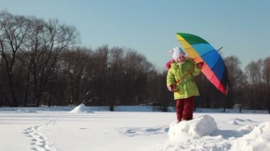 Girl stand on snow height and hold umbrella, she try to rotate it but lost balance — Stock Video