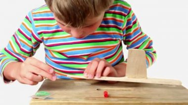 Boy apply adhesive and attach tail to wooden aircraft — Stock Video